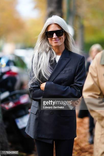 Sarah Harris wears sunglasses, a dark gray blazer jacket, a white top, outside Lacoste, during Paris Fashion Week - Womenswear Spring Summer 2020, on...
