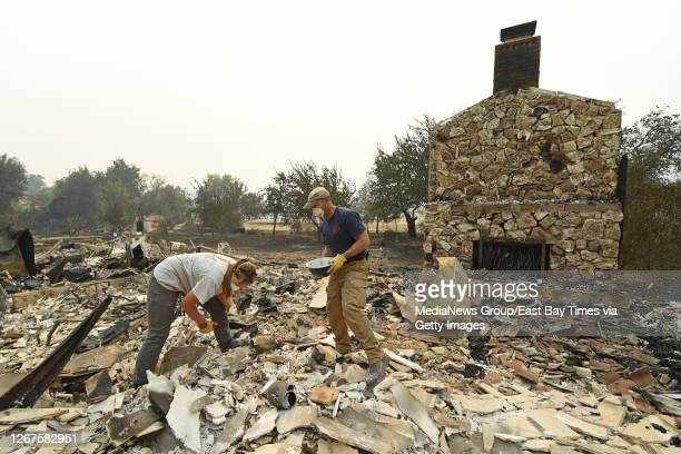 Sarah Hawkins, of Vacaville, and her husband Andy dig through the rubble after their home was destroyed by a fire in Vacaville, Calif., on Thursday,...
