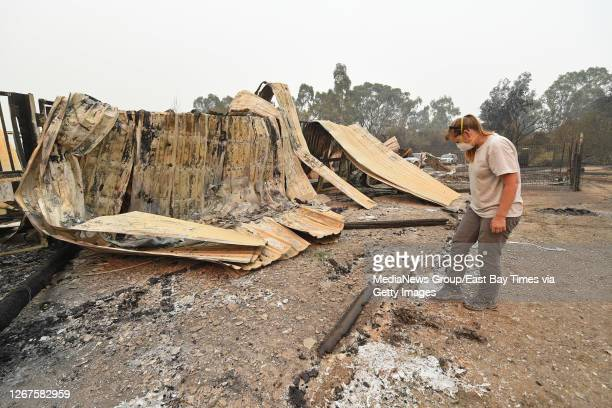 Sarah Hawkins, of Vacaville, examines the remains of her barn that was destroyed by a fire in Vacaville, Calif., on Thursday, Aug. 20, 2020. The LNU...