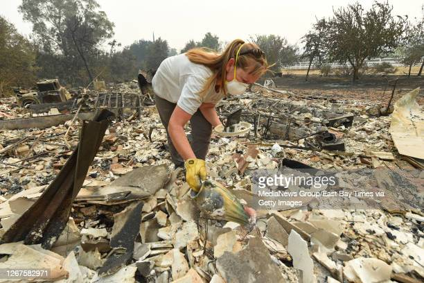 Sarah Hawkins, of Vacaville, finds a vase in the rubble after her home was destroyed by a fire in Vacaville, Calif., on Thursday, Aug. 20, 2020. The...
