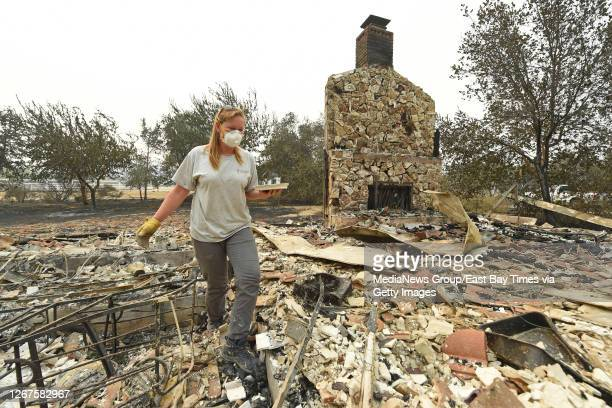 Sarah Hawkins, of Vacaville, searches through the rubble for belongings after her home was destroyed by a fire in Vacaville, Calif., on Thursday,...