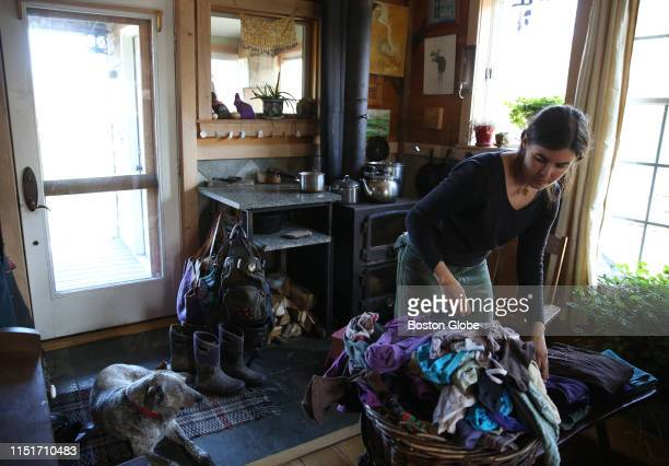 Sarah Hughes folds a pile of laundry fresh off the clothesline at her family's permaculture homestead in Belfast, ME on April 29, 2019. The family...