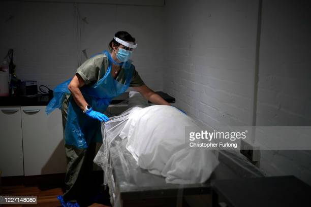 Sarah Hydes, an embalmer with Guardian Funerals, wears a face shield and other personal protective equipment while preparing a deceased person on May...