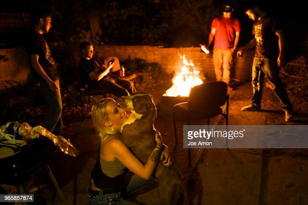 Sarah Janeczko 20 hugs one of her 3 dogs Marley a 2 year old pit bull beagle at home as the boys build a fire for burgers in the fire pit before...