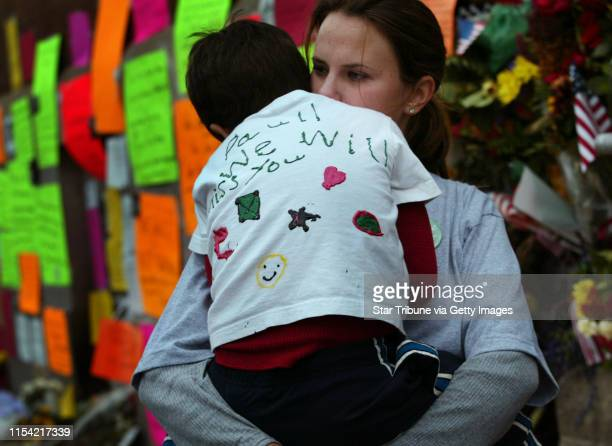 Sarah Jaremko of Brooklyn Park holds son Chaske Crawford as she looks at a fence outside Paul Wellstone's Campaign headquarters in St Paul that has...