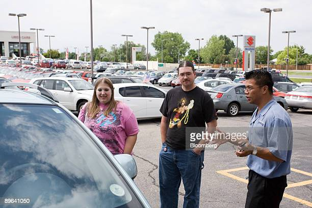 Sarah Jean Peters left and Neil Greenaway talk with salesman Bernard Quisumbing right prior to purchasing a Suzuki SX4 at Denver Isuzu Suzuki in...