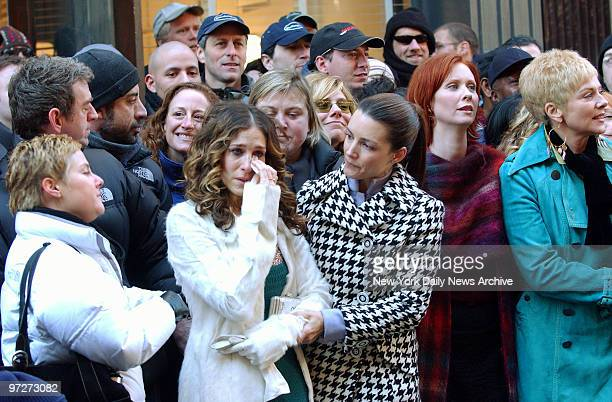 Sarah Jessica Parker wipes tears from her eyes as she's held by costar Kristin Davis in SoHo after finishing a scene for the last episode of Sex and...