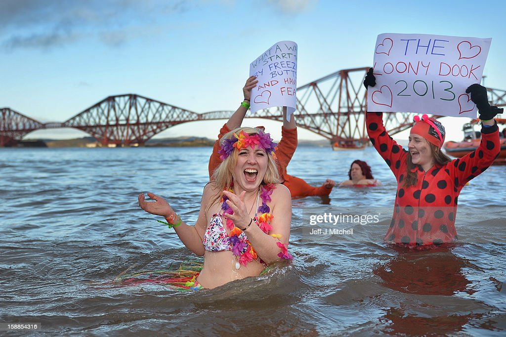 Sarah Johnston reacts to the water temperature as she joins around 1,000 New Year swimmers, many in costume, in front of the Forth Rail Bridge during the annual Loony Dook Swim in the River Forth on January 1, 2013 in South Queensferry, Scotland. Thousands of people gathered last night to see in the New Year at Hogmanay celebrations in towns and cities across Scotland.