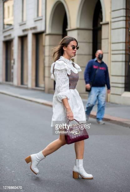 Sarah Lou seen wearing white dress, bordeaux bag outside Bally during the Milan Women's Fashion Week on September 26, 2020 in Milan, Italy.
