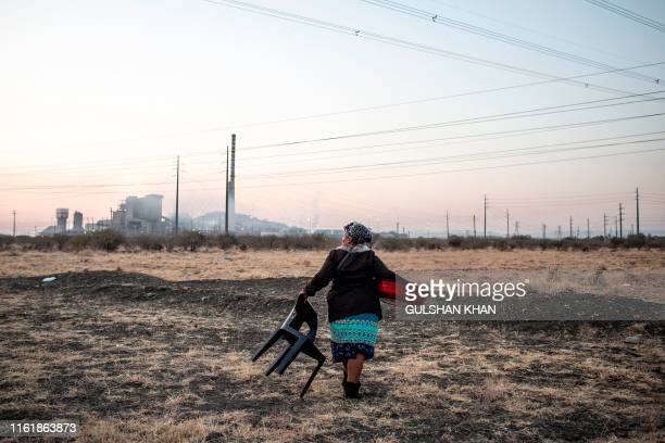 Sarah Matshwaya walks with her chair and a dish of cut cabbage to a spot where she will set up to cook and sell food close to the former Lonmin owned...