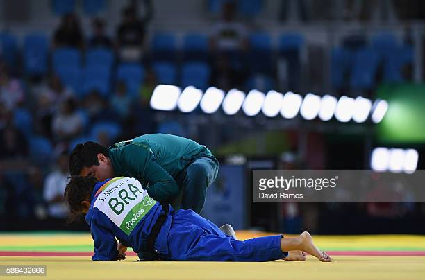 Sarah Menezes of Brazil is tended to after being defeated by Urantsetseg Munkhbat of Mongolia during the Women's 48 kg Repechage Judo contest on Day...