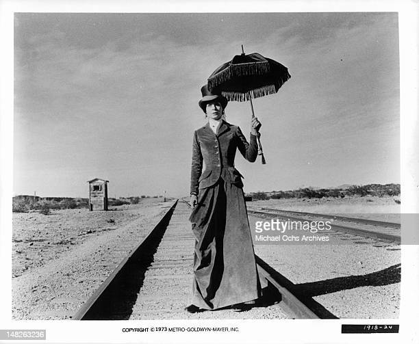 Sarah Miles carrying sunbrella on railroad tracks in a scene from the film 'The Man Who Loved Cat Dancing' 1973