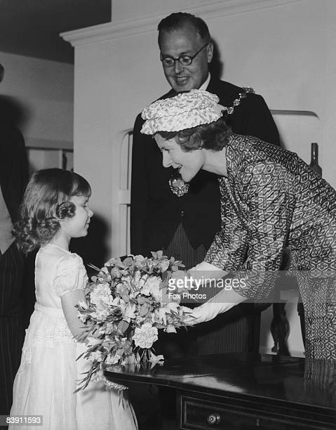 Sarah Osborn 6yearold daughter of Sir Danvers and Lady Osborn presents a bouquet to Lady Eden at the opening of the Antique Dealers' Fair at...