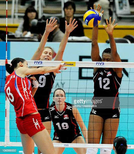 Sarah Pavan and Sherline Holness of Canada try to block a spike from Nataliya Goncharova of Russia while their teammate Lauren O'Reilly looks on...