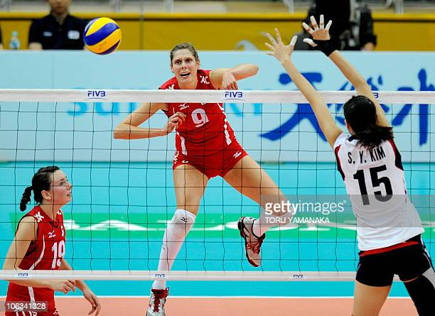 Sarah Pavan of Canada spikes the ball over Kim SeYoung of South Korea as Lauren O'Reilly of Canada looks on during their first round match of the...