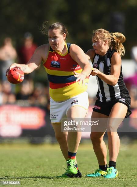 Sarah Perkins of the Crows kicks whilst being tackled during the round seven AFLW match between the Collingwood Magpies and the Adelaide Crows at...
