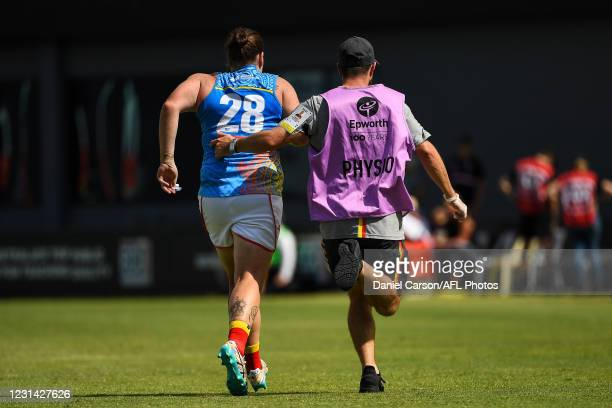 Sarah Perkins of the Suns is escorted off with an injury during the 2021 AFLW Round 05 match between the West Coast Eagles and the Gold Coast Suns at...