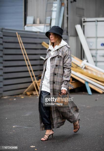 Sarah Schäfer is seen wearing bucket hat, plaid trench coat, hoody, black leather pants outside Munthe during Copenhagen Fashion Week Spring/Summer...