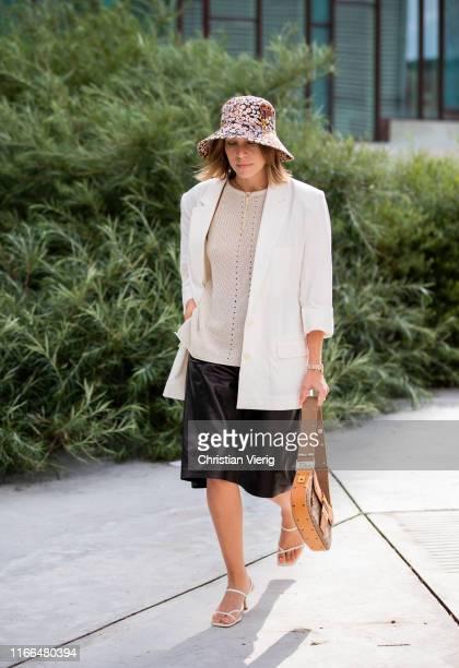 Sarah Schäfer is seen wearing hat with floral print, vintage Dior bag, white blazer, black pants, sandals outside Brøgger during Copenhagen Fashion...