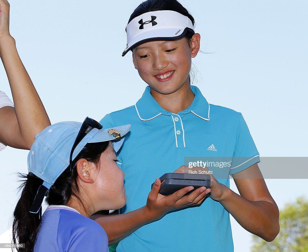 Sarah Shao looks at her sister Christines medal after she wins the Girls 12-13 championship at a regional round of the Drive, Chip and Putt Championship at Bethpage Green on August 27, 2014 at Eisenhower Park Golf Club in Farmingdale, New York.