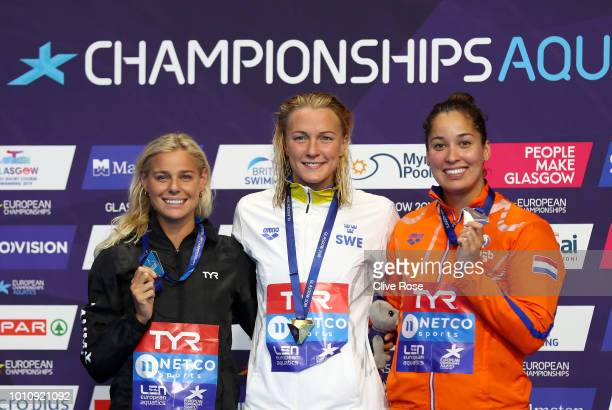Sarah Sjoestroem of Sweden celebrates victory in the Women's 50m Freestyle Swimming Final with her Gold Medal posing with Silver Medalist Pernille...