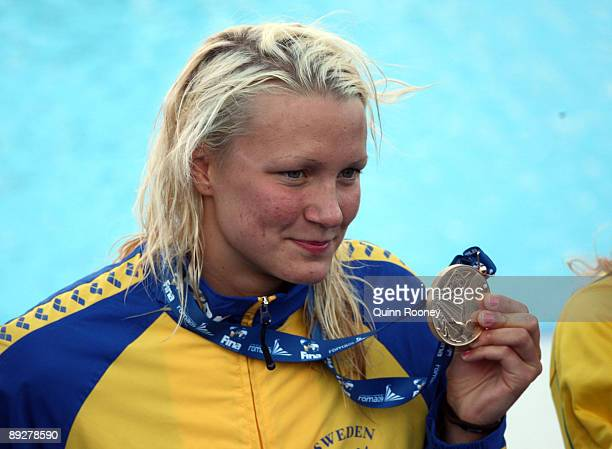 Sarah Sjostrom of Sweden smiles at the crowd as she receives the gold medal during the medal ceremony for the Women's 100m Butterfly Final during the...