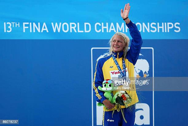 Sarah Sjostrom of Sweden waves to the crowd as she receives the gold medal during the medal ceremony for the Women's 100m Butterfly Final during the...