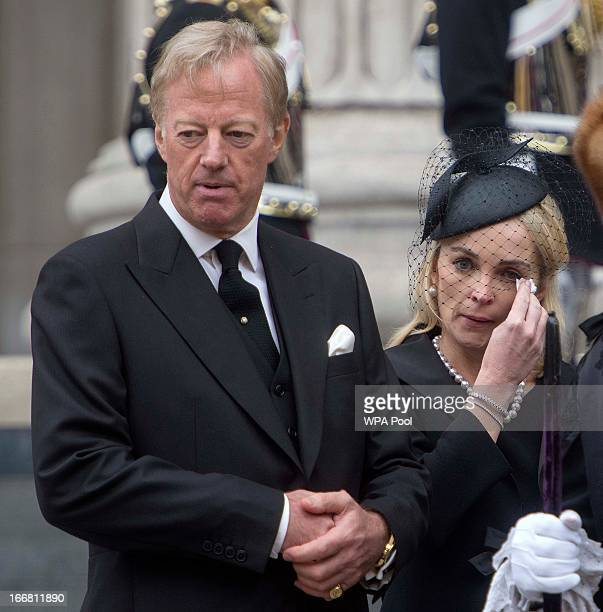 Sarah Thatcher wipes a tear from her eye as she stands next to her husband Mark Thatcher whilst they watch the coffin of former British Prime...