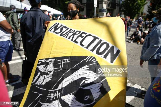 Sarah Tornai holds an insurrection flag that Human Rights Attorney Mike Withey saved from the WTO Seattle protests as people gather in the newly...