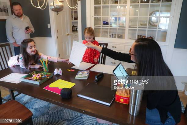 Sarah Yunits checks her daugher Ada's homework while Cora waits her turn as dad Conor Yunits is on a work conference call at their home in Brockton...