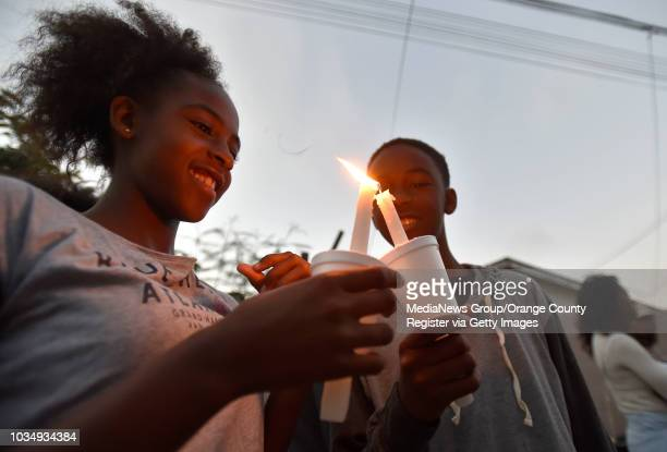Sarai Terrell left helps her brother Shon light his candle as they gather for a vigil in Long Beach CA on Friday June 24 2016 Family and close...