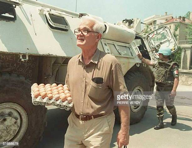 """Sarajevan carrying eggs crosses """"sniper alley"""" shielded by a UN APC 15 June. Heavy fighting has broken out 15 June north of the Bosnian capital,..."""