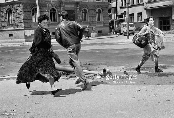 Sarajevans run for cover during shooting in 'Sniper Alley' in July 1992.