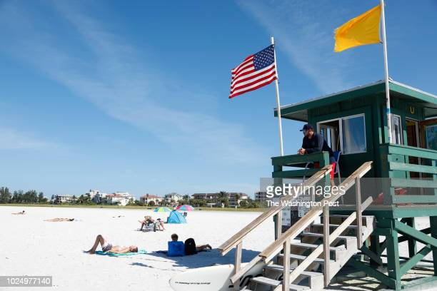 August 26: Sarasota County Emergency Services lifeguard lieutenant Drew Bittle patrols the area at Siesta Beach on August 26, 2018 in Siesta Key,...