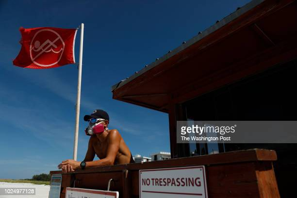Sarasota County Emergency Services lifeguard Mariano Martinez wears a mask because of red tide at Lido Beach on August 26 2018 in Sarasota Florida...