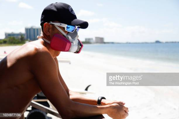 August 26: Sarasota County Emergency Services lifeguard Mariano Martinez wears a mask because of red tide at Lido Beach on August 26, 2018 in...