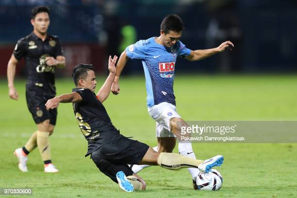 Sarawut Masuk of Bangkok Glass FC is tackled by Suchao Nutnum of Buriram United FC during the Thai League 1 match between Bangkok Glass FC and...