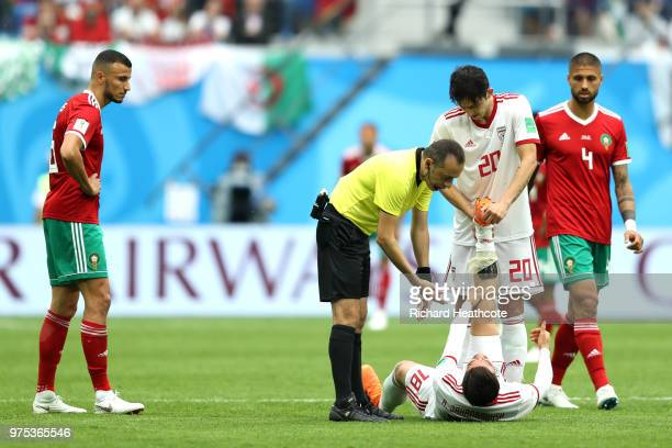 Sardar Azmoun of Iran helps team mate Alireza Jahanbakhsh to recoverfrom cramps during the 2018 FIFA World Cup Russia group B match between Morocco...