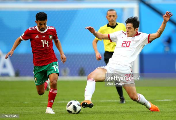Sardar Azmoun of Iran tackles Mbark Boussoufa of Morocco during the 2018 FIFA World Cup Russia group B match between Morocco and Iran at Saint...