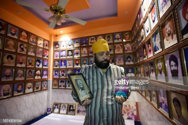 Sardar Kanwaljeet Singh Sandhu holds the photographs of his brothers who were killed during the 1984 Sikh massacre at Trilokpuri on December 17 2018...