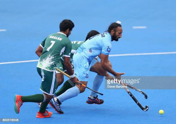 Sardar Singh of India breaks away from Muhammad Dilber of Pakistan and Muhammad Arslan Qadir of Pakistan during the 5th8th place match between...