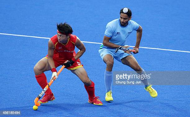 Sardar Singh of India competes for the ball with Wang Zipeng of China during the Hockey Men's Pool B match between India and China during the 2014...