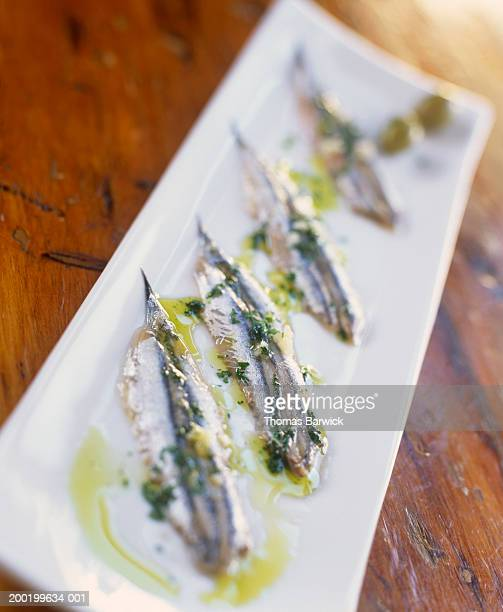 Sardines marinated in garlic, olive oil and salt on serving tray