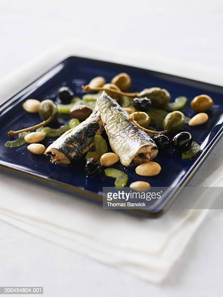 Sardines with celery salad, caper berries, Spanish almonds and olives