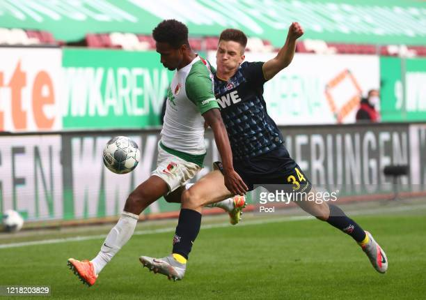 Sarenren Bazee of FC Augsburg is challenged by Noah Katterbach of 1. FC Koeln during the Bundesliga match between FC Augsburg and 1. FC Koeln at...
