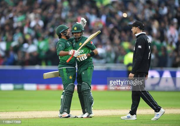 Sarfaraz Ahmed and Babar Azam of Pakistan celebrate victory as Mitchell Santner of New Zealand looks on during the Group Stage match of the ICC...