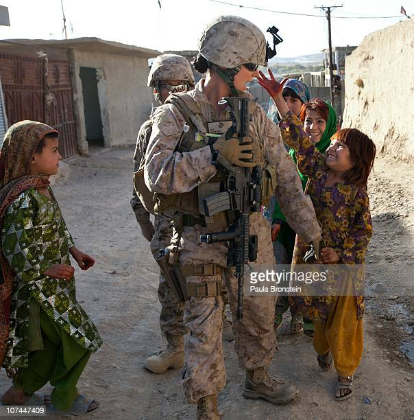 Sargent Sheena Adams US Marine with the FET 1st Battalion 8th Marines Regimental Combat team II gets attention from some Afghan girls while on patrol...
