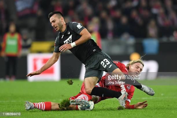 Sargis Adamyan of TSG 1899 Hoffenheim is challenged by Sebastiaan Bornauw of 1. FC Koeln during the Bundesliga match between 1. FC Koeln and TSG 1899...