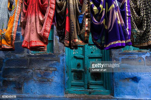 sari hanging on clothesline by house - sari stock pictures, royalty-free photos & images