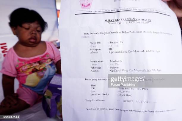 Sari Rezita Ariyanti and her birth certificate at home in Pidie Jaya Indonesia MEASURING 87cm in height and weighing 20kg Sari Rezita Ariyanti looks...